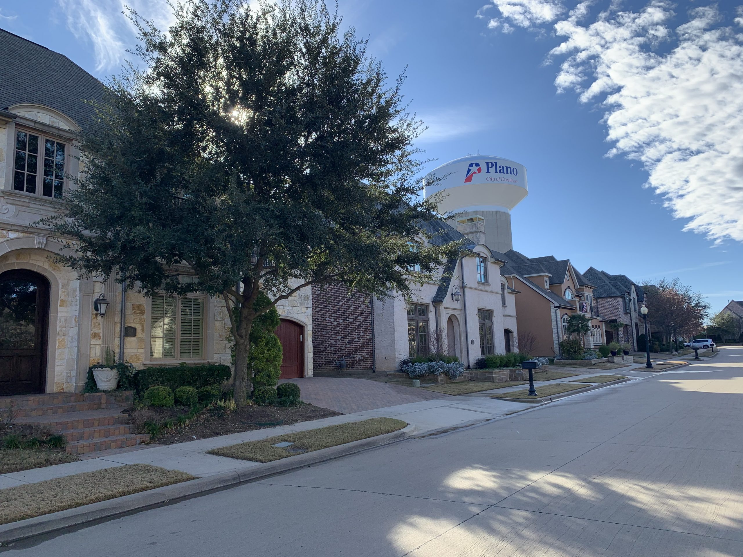 Residential street with houses, a tree, and a Plano water tower in the background.
